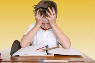 Boy with head in hands doing homework