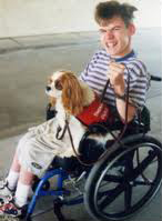 man in wheelchair with dog on lead